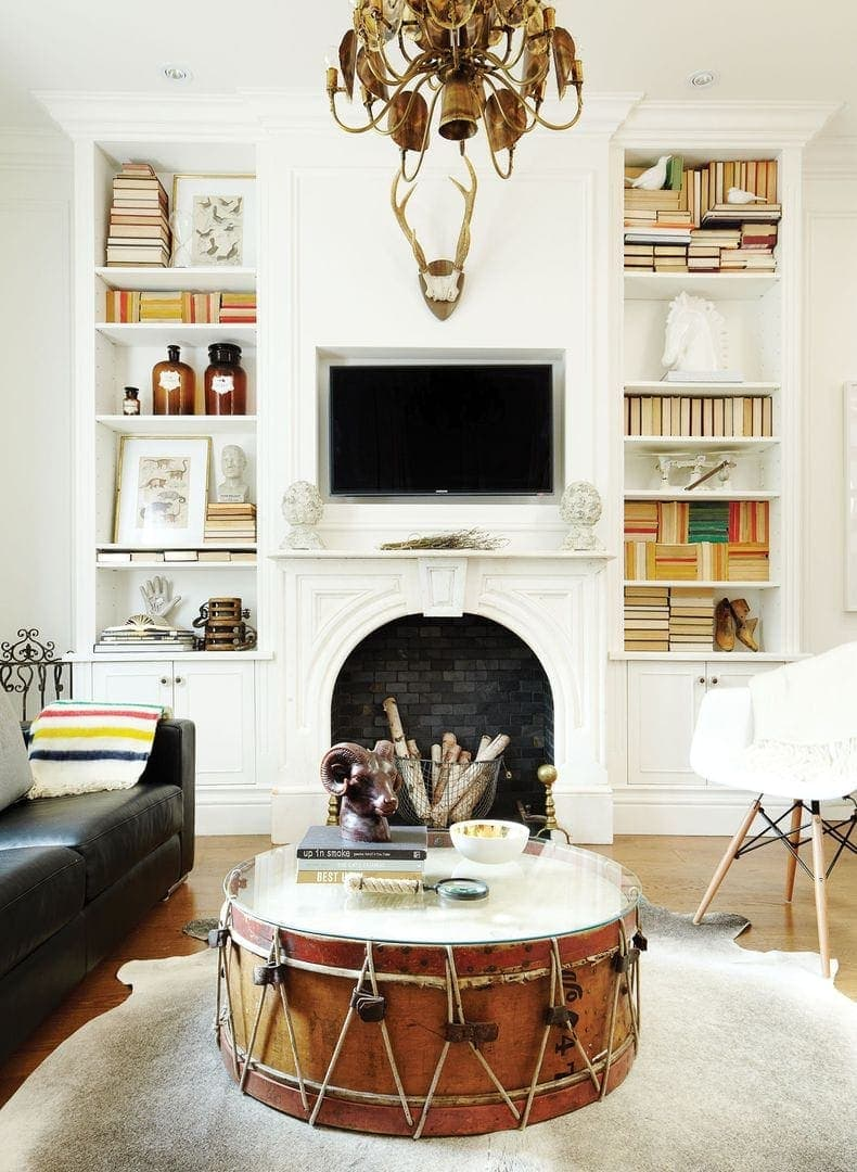 vintage drum used as a coffee table in living room with fireplace