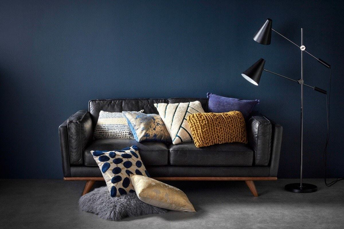 black leather sofa against dark blue feature wall with lots of cushions from Freedom