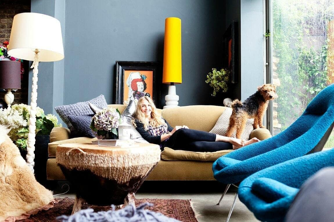 abigail ahern's home with abigail ahern on her brown sofa with dog and two blue armchairs
