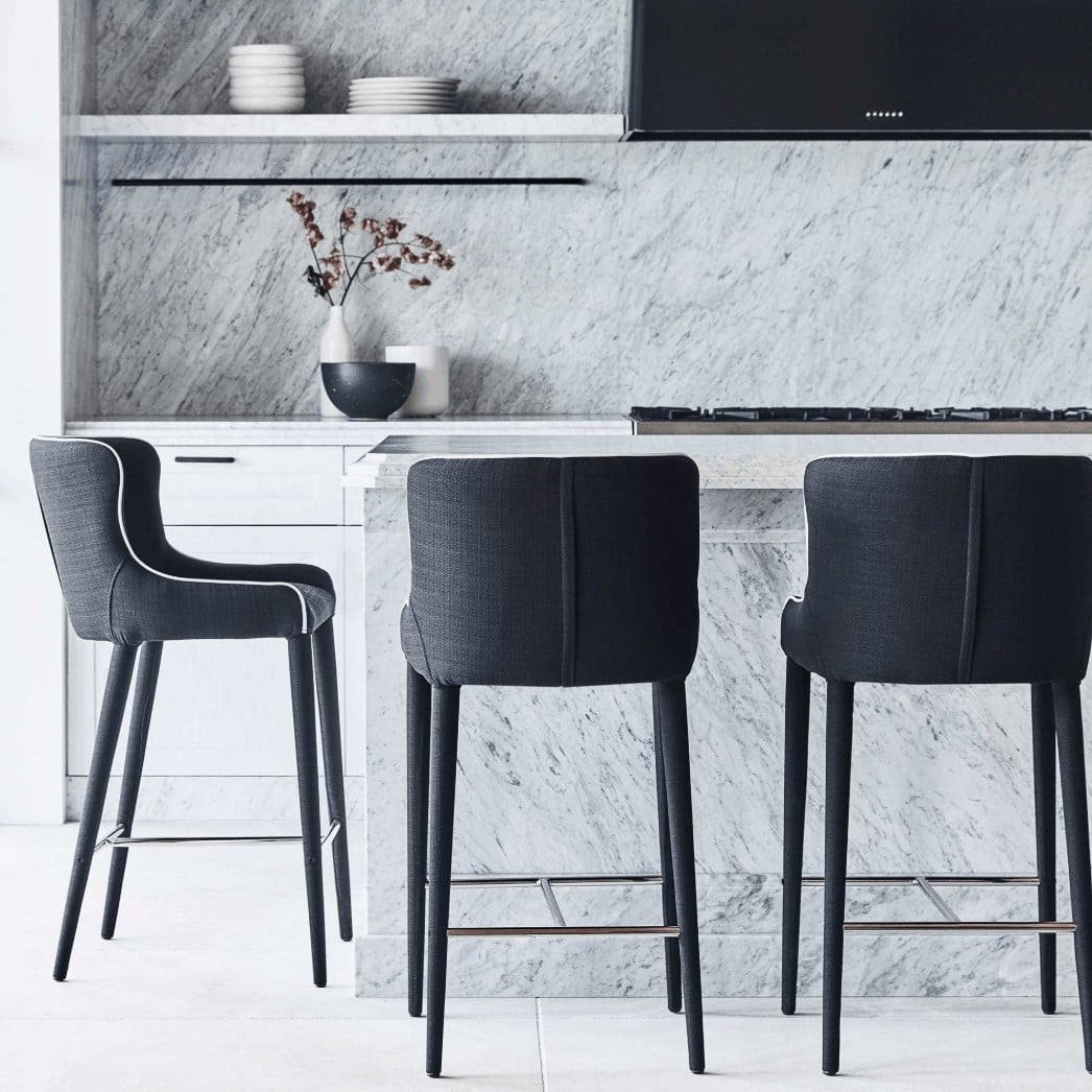 coco republic grey upholstered bar stools in white marble kitchen