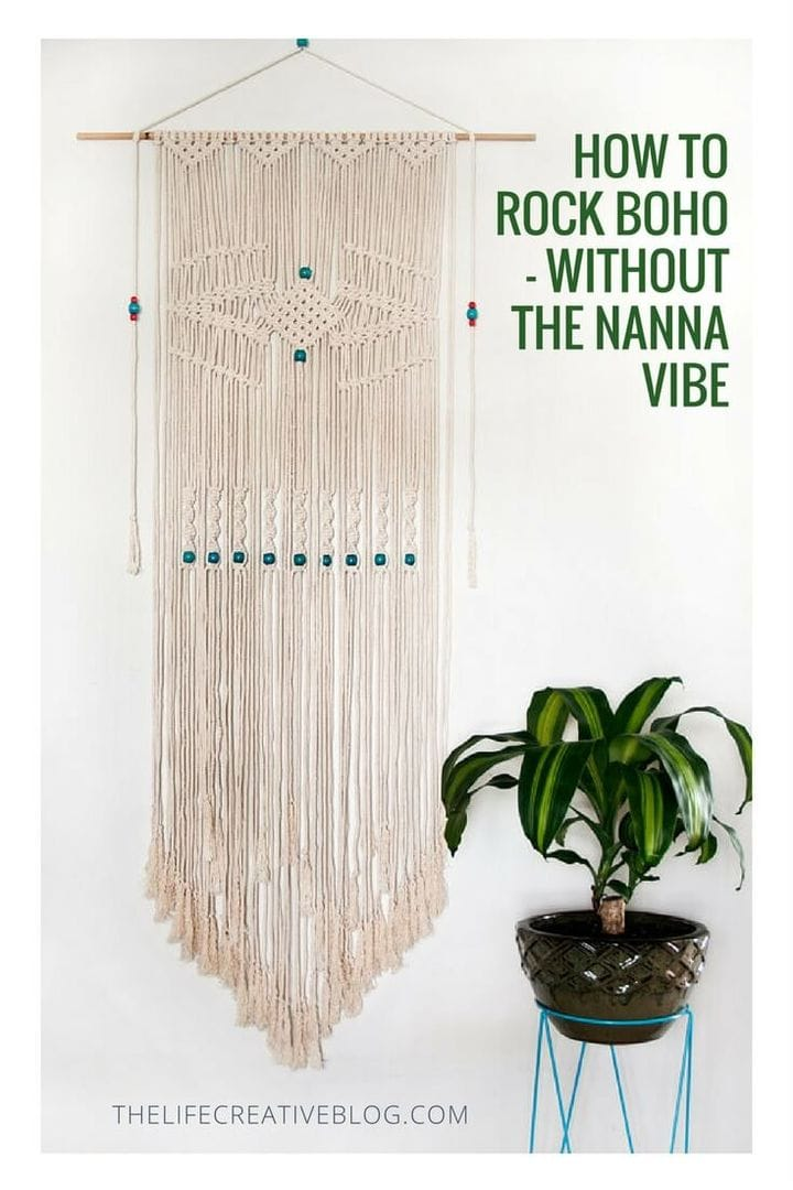 long vertical white macrame wall hanging and lush green plant in pot with bright blue pot stand