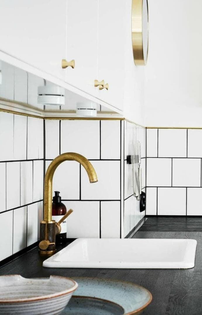 Brass decor brass tapware in kitchen with white subway tiles