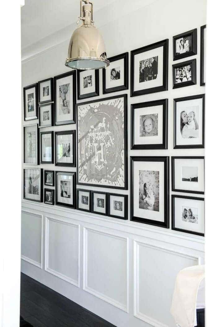 Gallery wall photo wall in hallway with black and white photos TLC Interiors