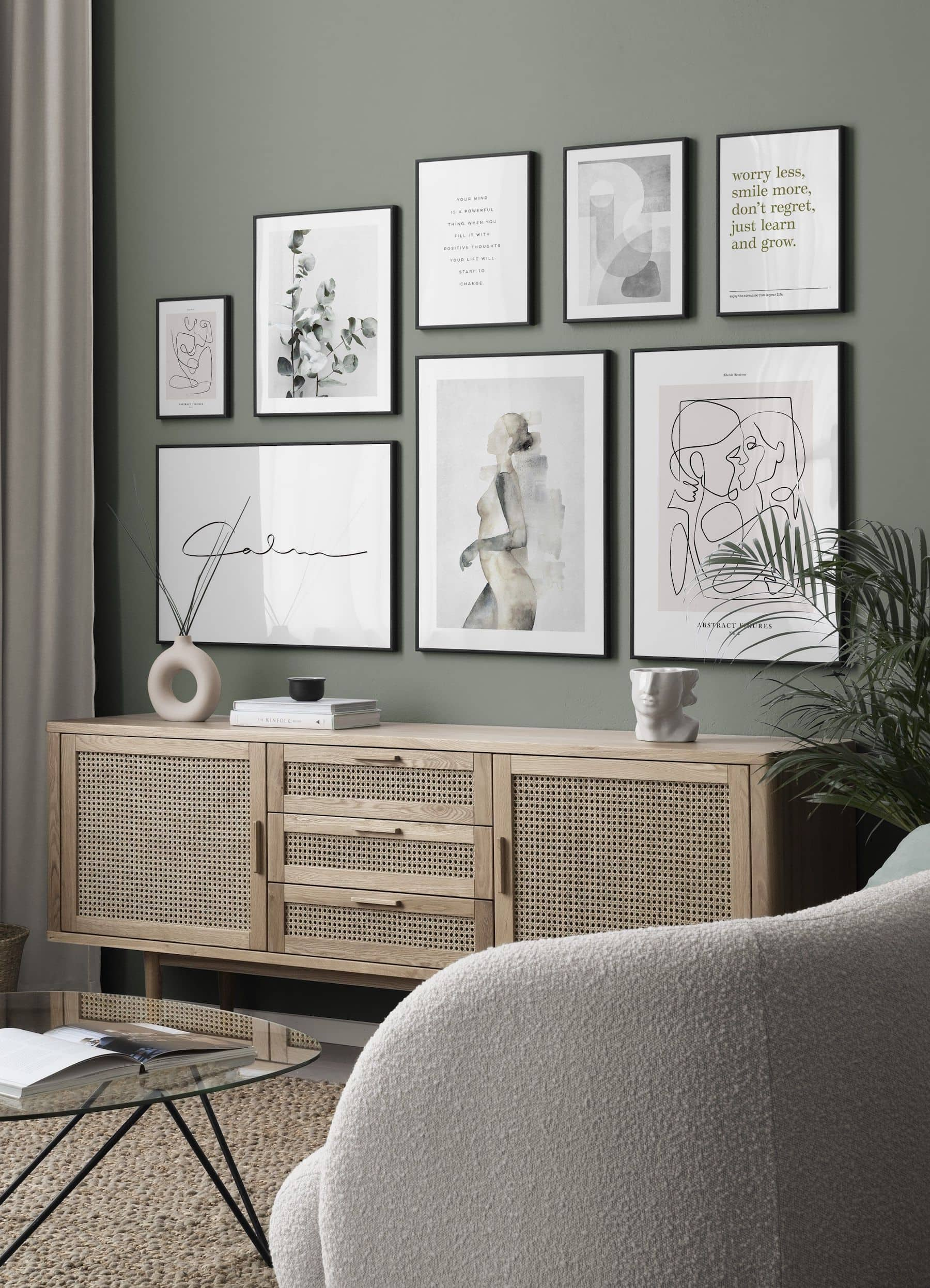 gallery wall of art above rattan sideboard on green feature wall desenio