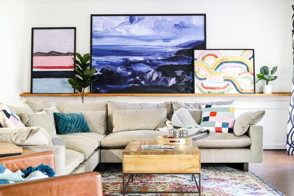 gallery wall on picture ledges in bright living room