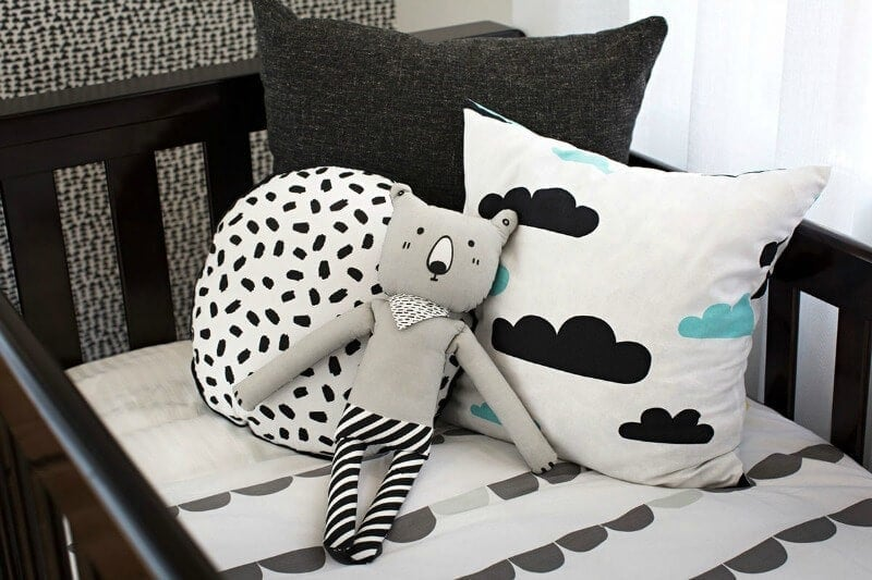 black and white nursery bedding with cloud cushion cover in brown cot