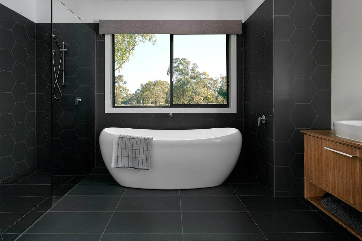 black bathroom hexagonal black wall tiles freestanding bath with view from metricon