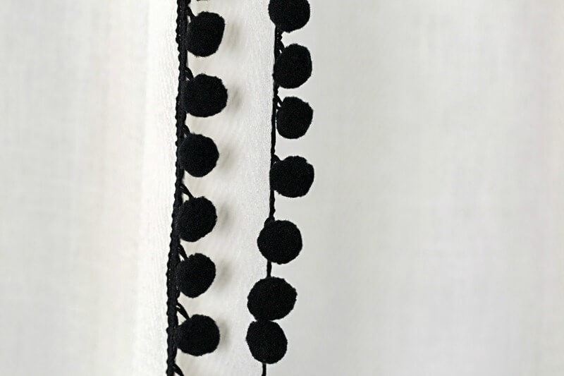 black pom pom trim on white sheer curtain in kids nusery