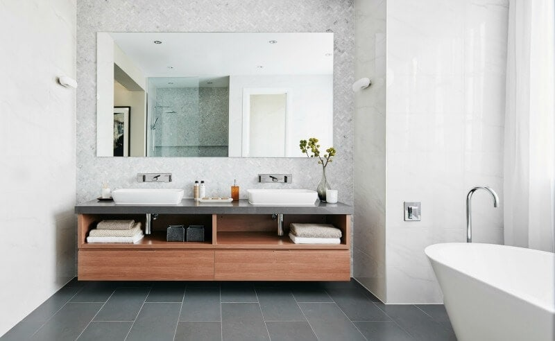 floating bathroom vanity in warm timber with herringbone marble wall tiles from metricon