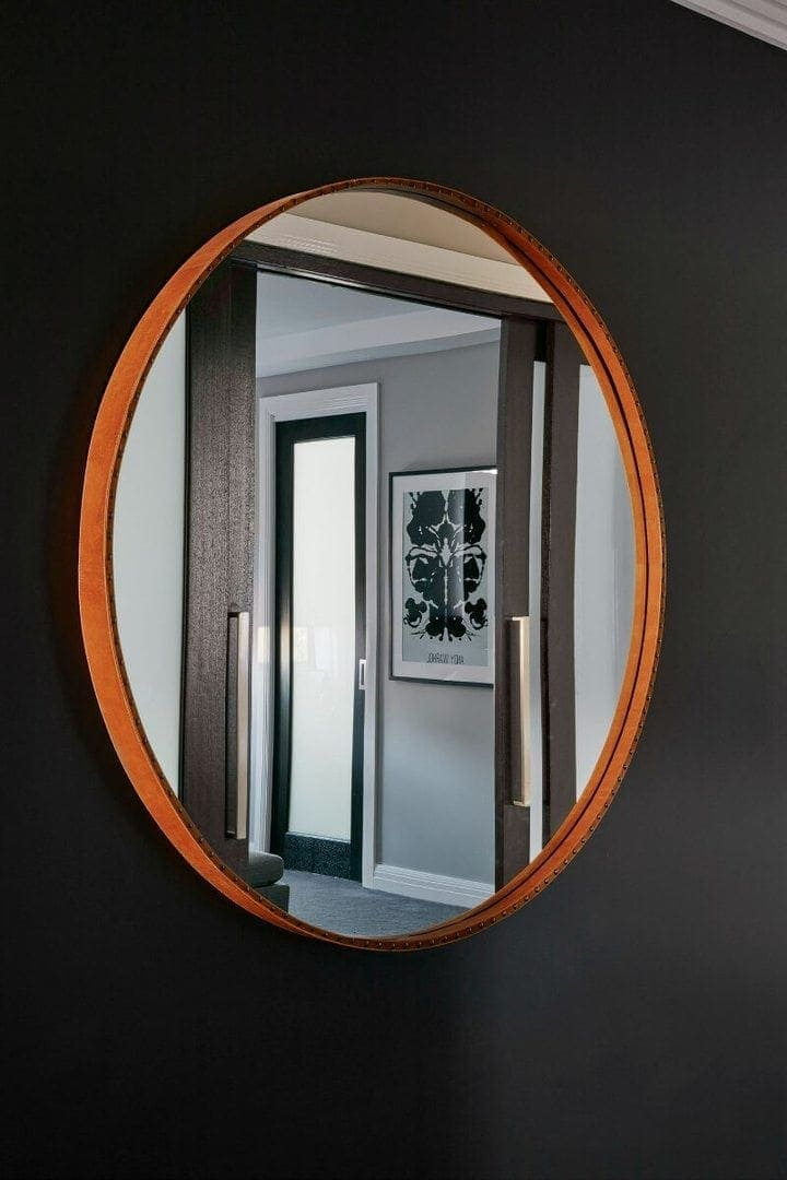 round leather mirror on black paint feature wall from metricon