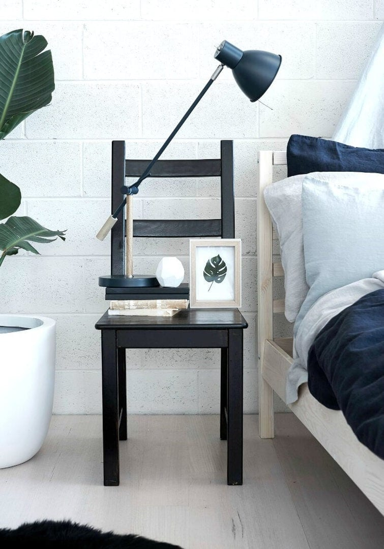 scandinavian bedroom black chair as bedside table with blue linen bedding