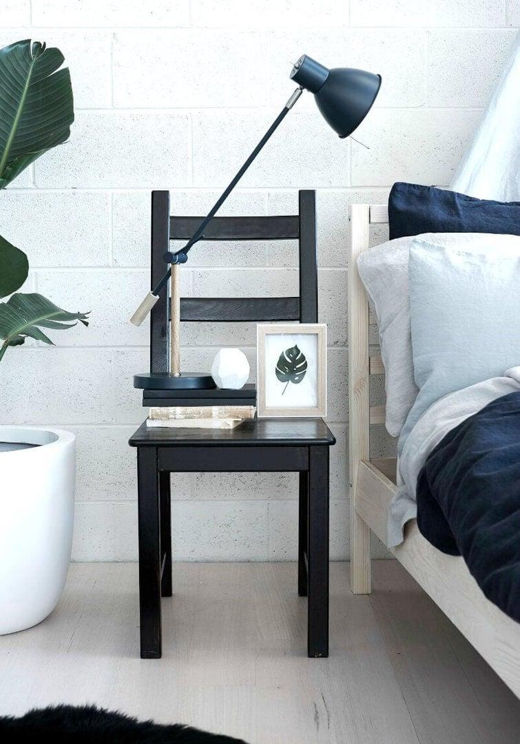 scandinavian bedroom black chair as bedside table with blue linen bedding