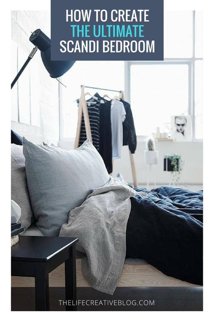 scandinavian bedroom with dark blue linen sheet set on white timber bed from ikea