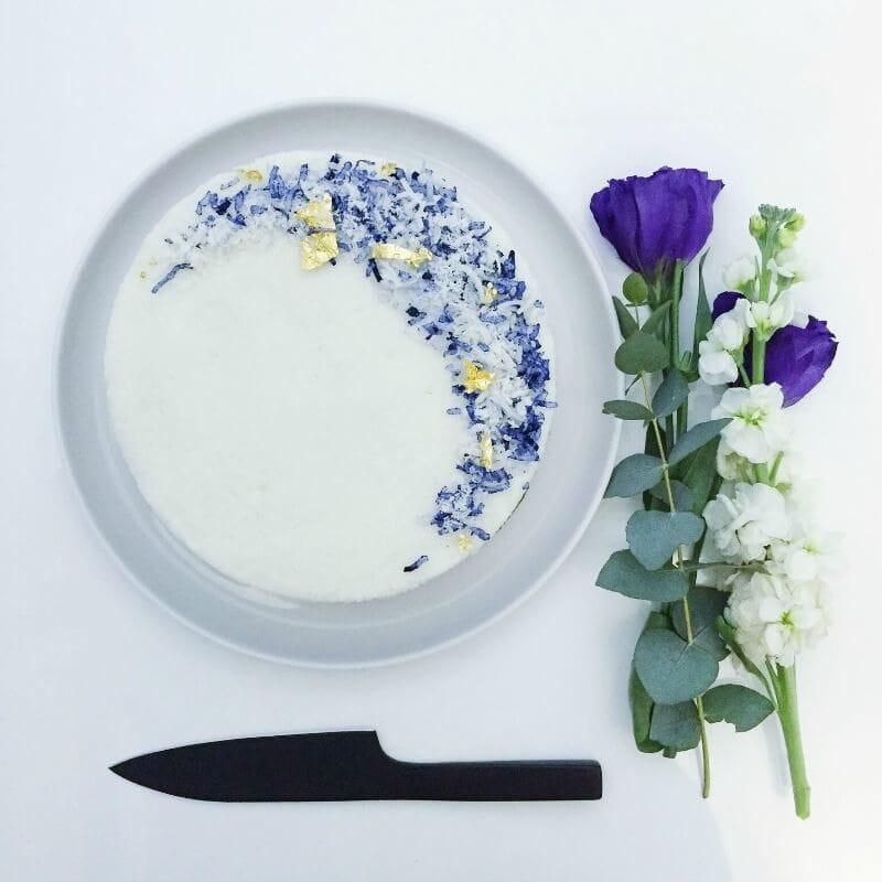 vegan coconut cake recipe white cake flatlay photo with black knife and purple rose