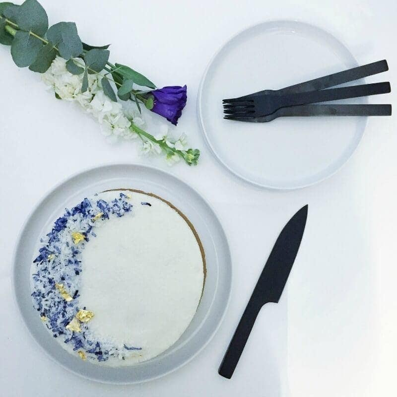 white vegan coconut cake with purple icing and black cutlery flatlay food stylingwhite vegan coconut cake with purple icing and black cutlery flatlay food styling