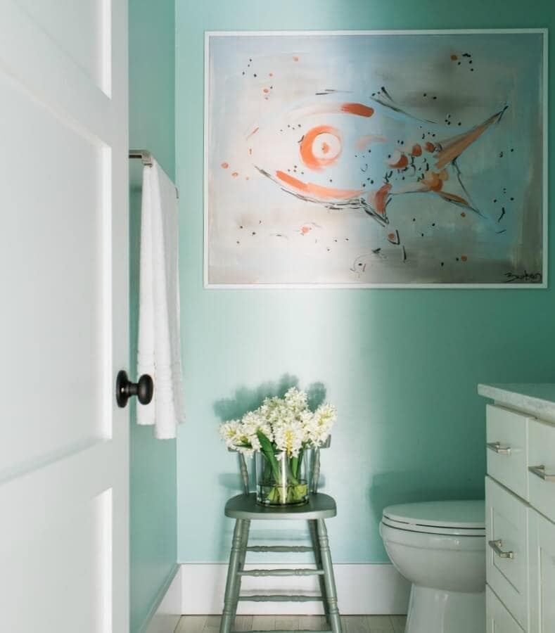 abstract art in powder room with turquoise walls and flowers on stool