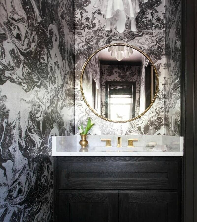 black and white marble wallpaper design in powder room with round gold mirror