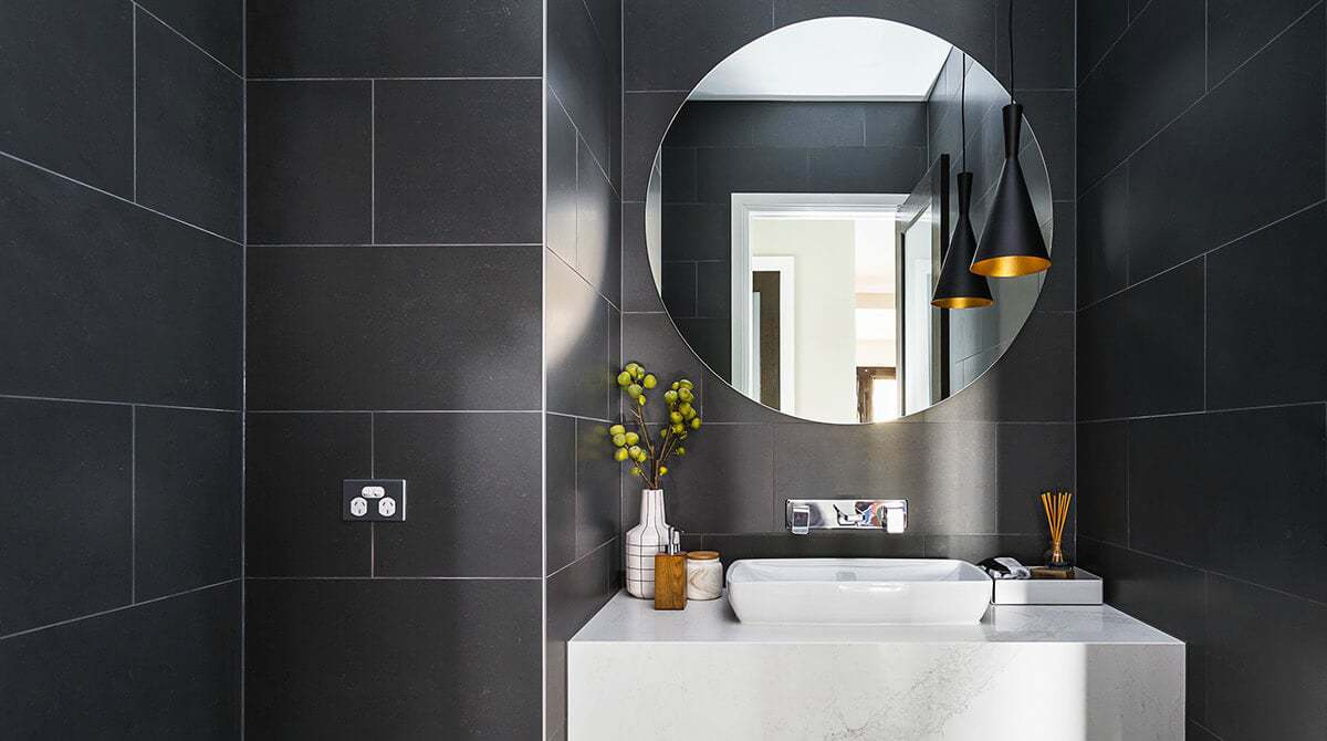 black tile powder room design with round mirror from metricon