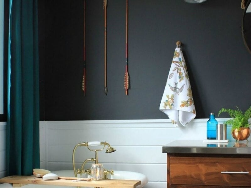 black walls in bathroom with gold tapware and brown timber cabinetry