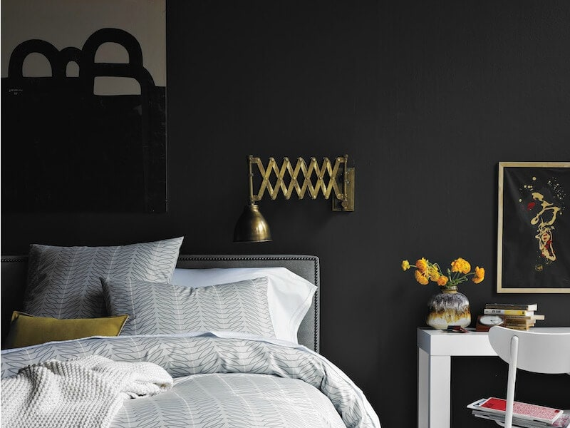 black walls in bedroom with grey white and yellow accents