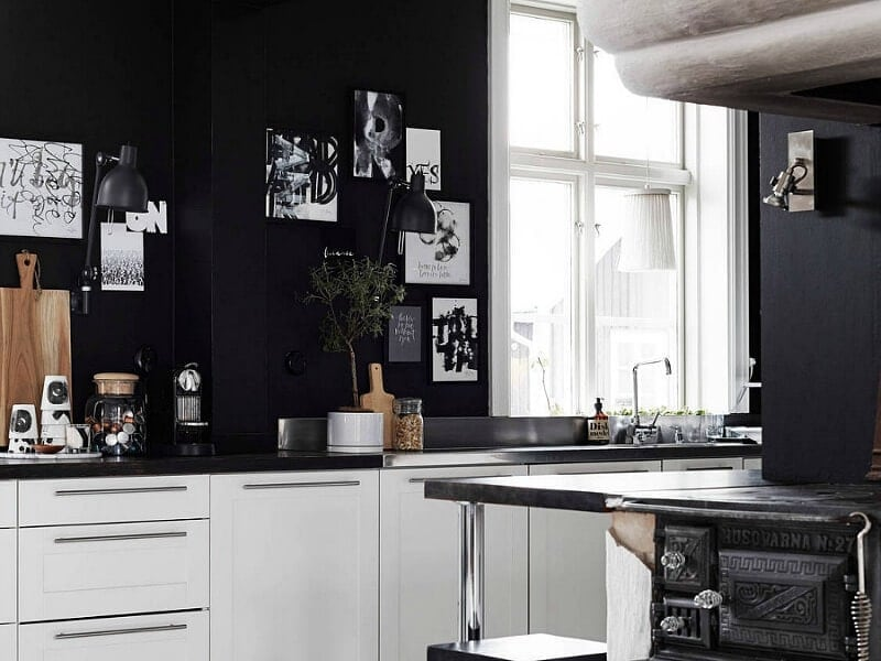 black walls in kitchen with white kitchen cabinetry and silver handles
