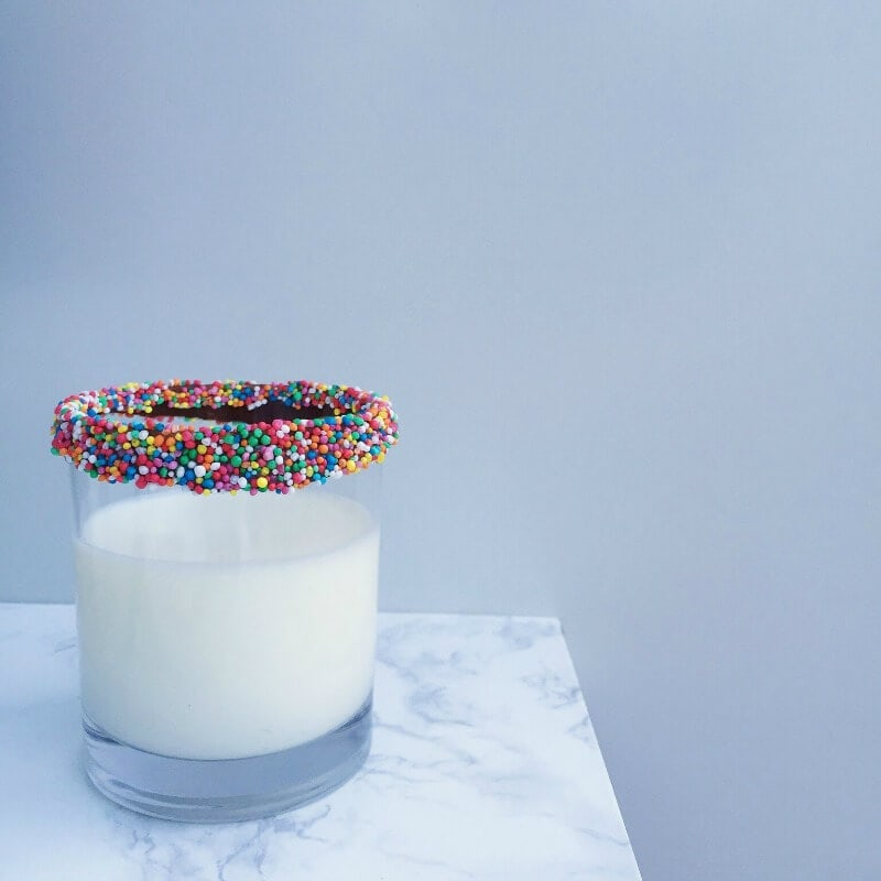 milk in glass with chocolate and sprinkles around the rim