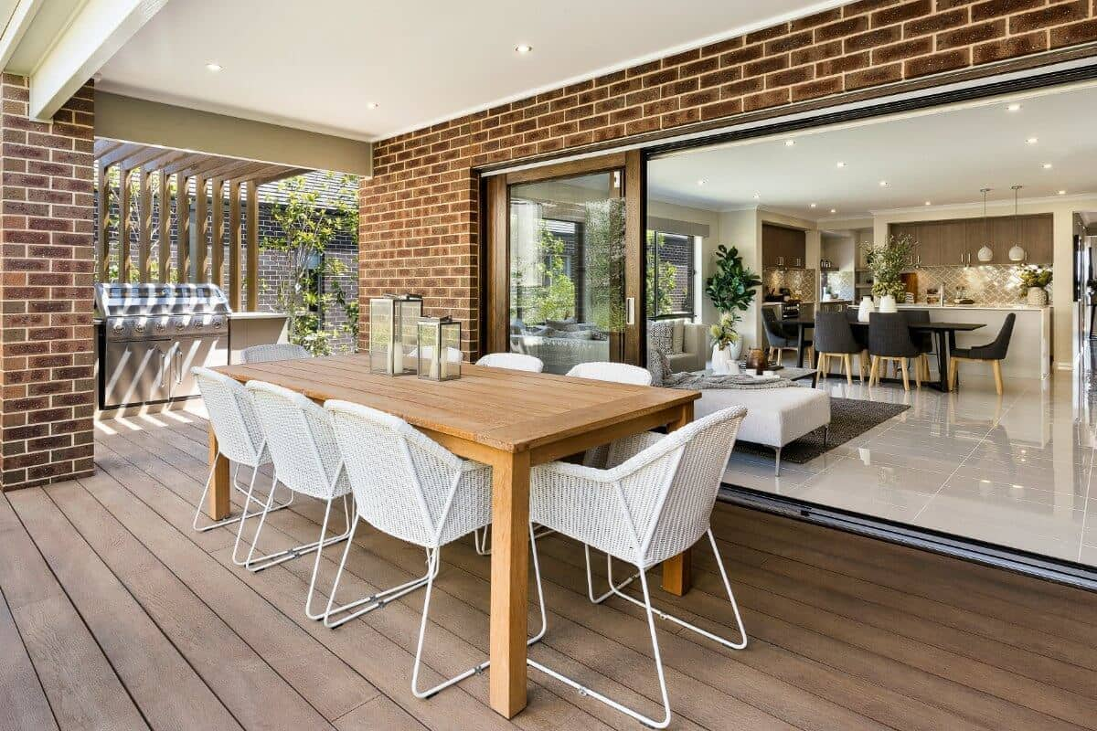 outdoor room with timber floor brown brick and white outdoor dining chairs by metricon
