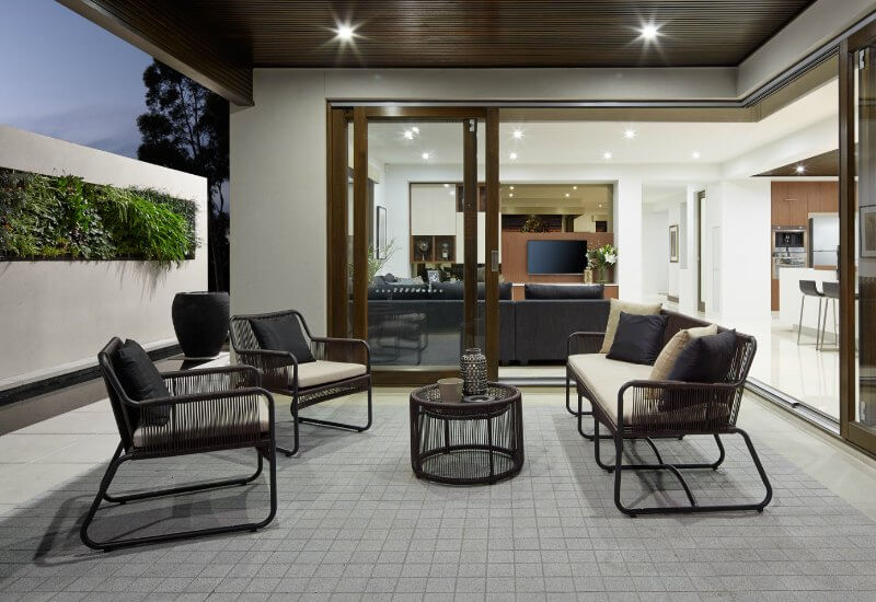 outdoor room with vertical garden and dark outdoor furniture setting by metricon homes