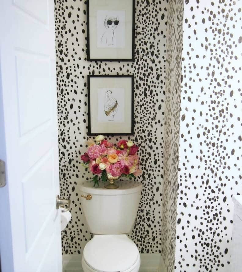 powder room design with black and white polka dot wallpaper and flowers on toilet