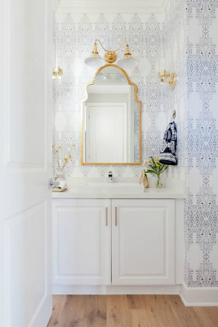 powder room wallpaper with gold mirror and gold wall sconces