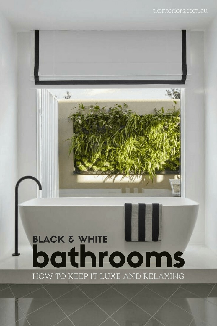 luxe black and white bathroom with freestanding tub and matte black tapware