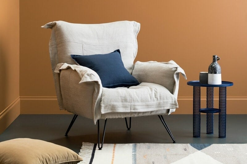 haymes-paint-strata-orange-wall-with-muted-armchair-and-blue-cushion