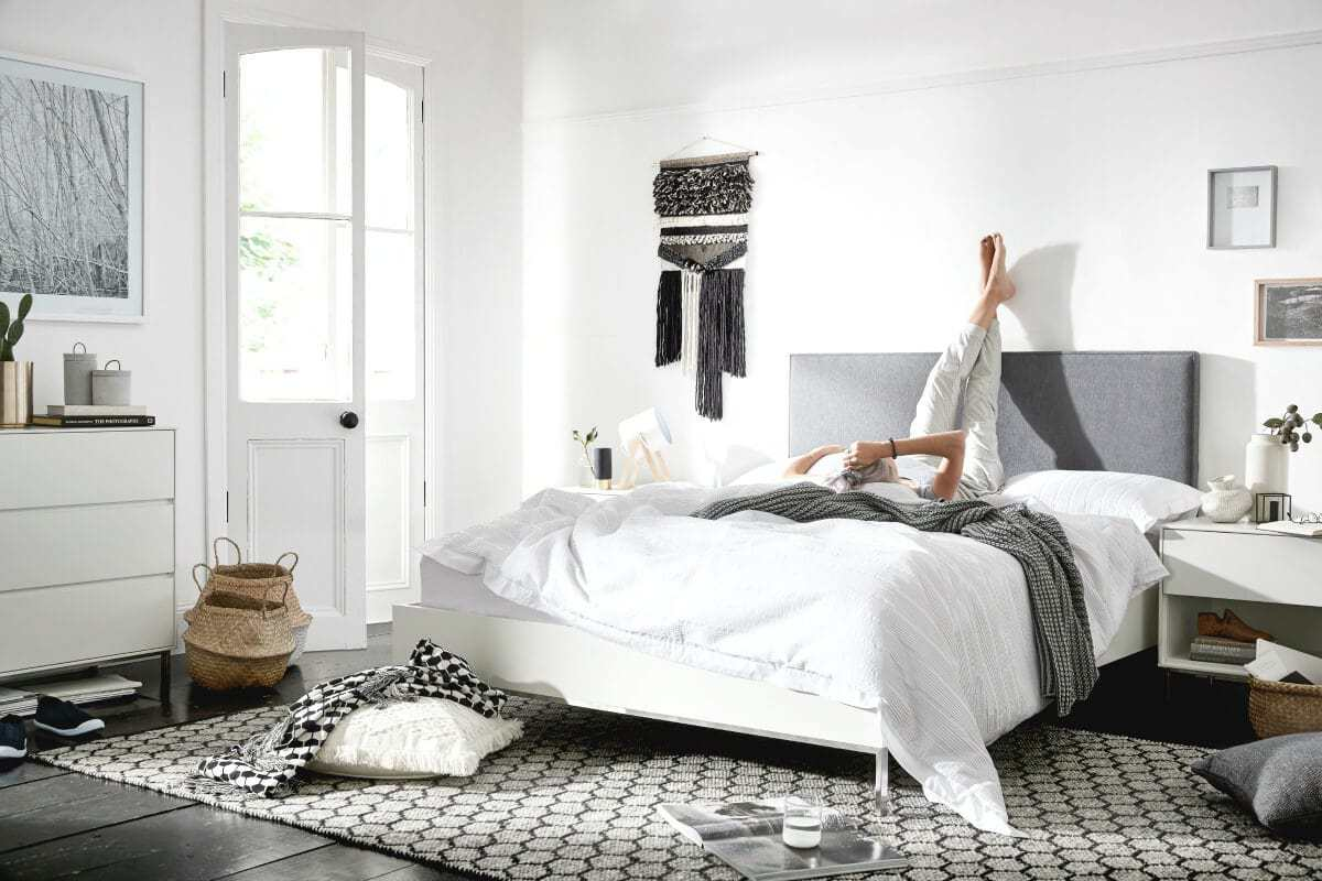 black and white bedroom with grey upholstered headboard macrame wall hanger and belly baskets