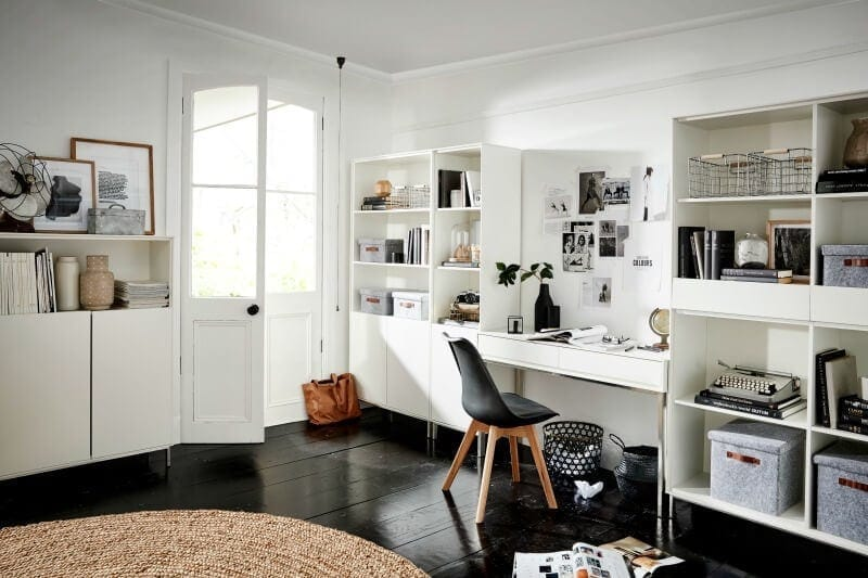 black and white bedroom with white desk and shelves and round jute rug