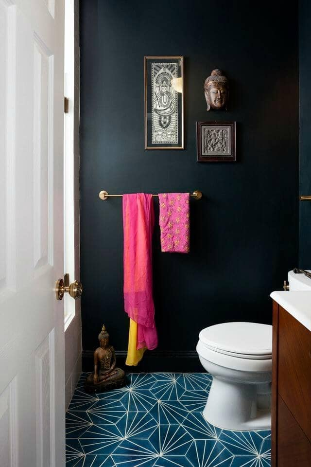 black bathroom with hot pink towels and ethnic decor and art