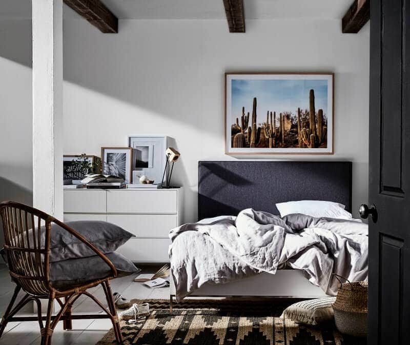 Modern black and white bedroom with desert art above bed and aztec print rug