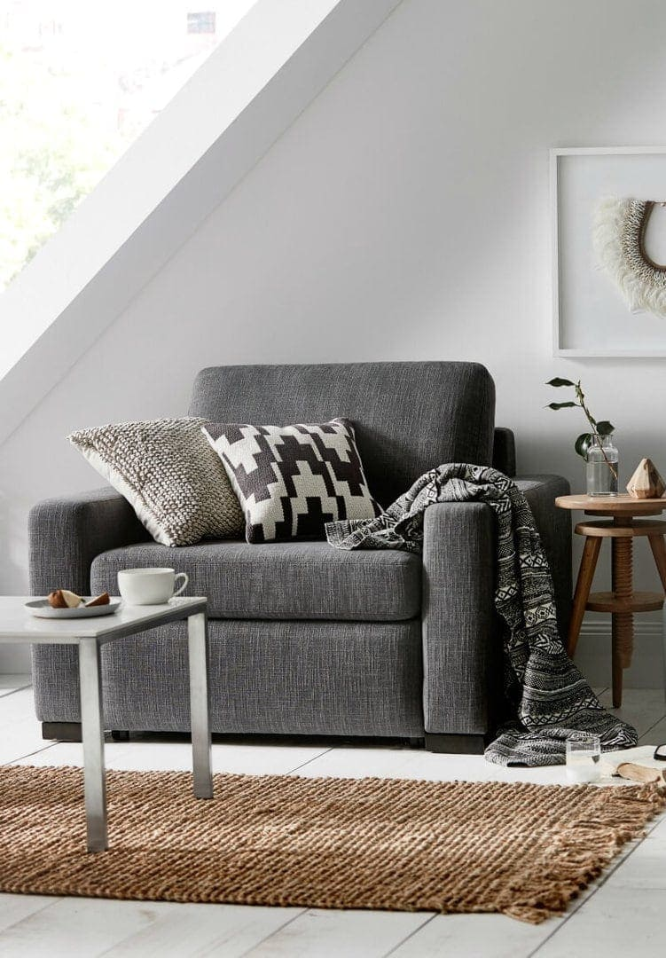 upholstered grey armchair with aztec print throw and jute rug from freedom