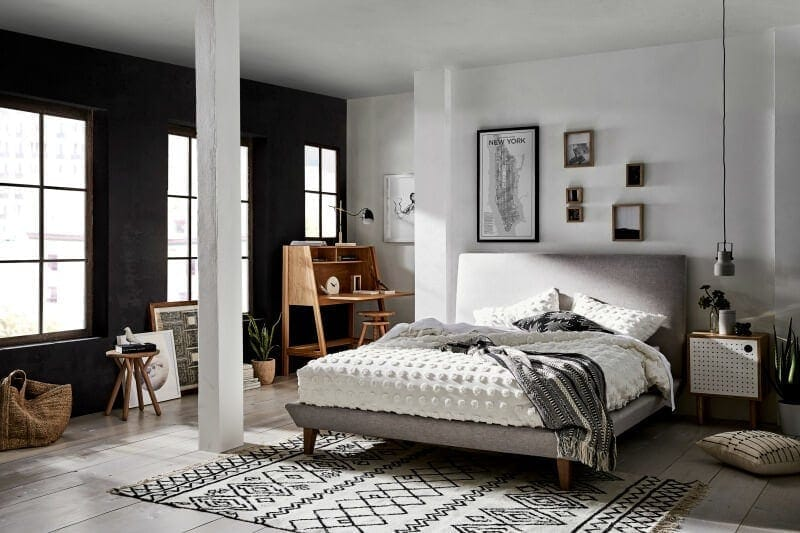 warehouse apartment black and white bedroom with black feature wall and grey bed