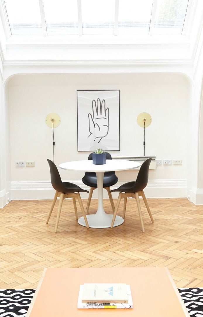 black dining chairs around white dining table and herringbone floor