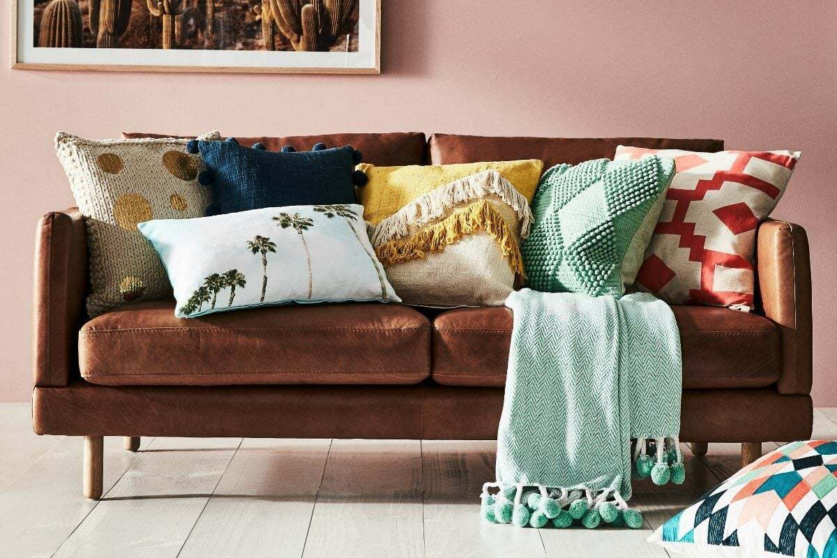 brown leather sofa from freedom with lots of cushions and a turquoise throw with pom poms