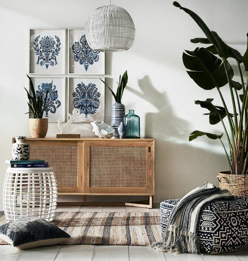 coastal bohemian interior design with blonde timber sideboard and large indoor plant