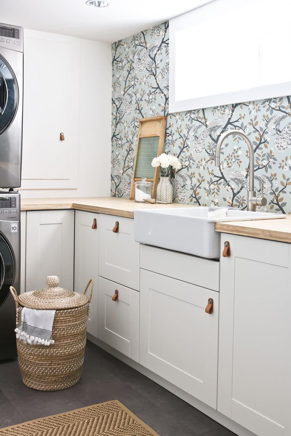 laundry room with floral wallpaper design and leather handles on cabinets