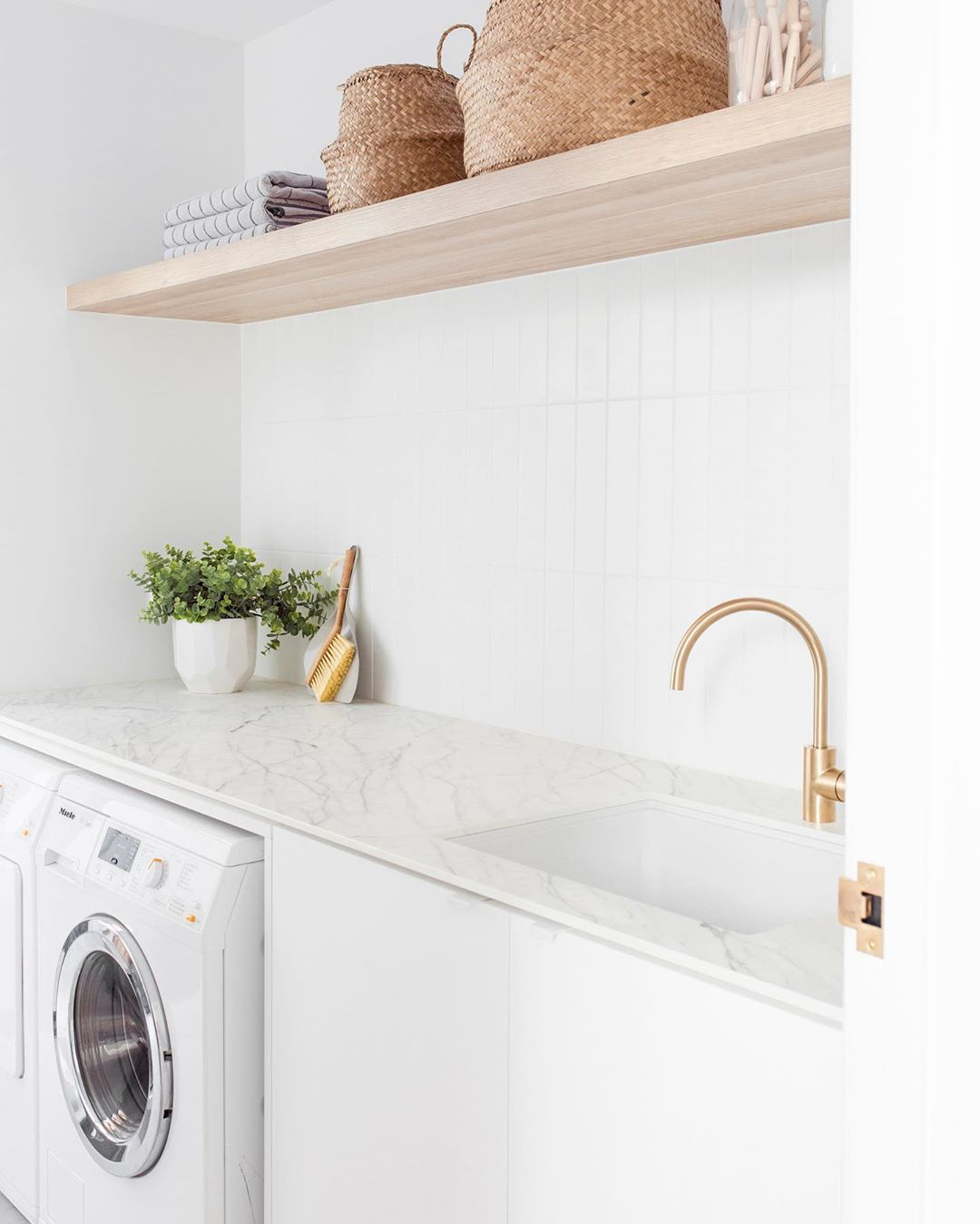 laundry with floating shelves and gold tapware abi interiors
