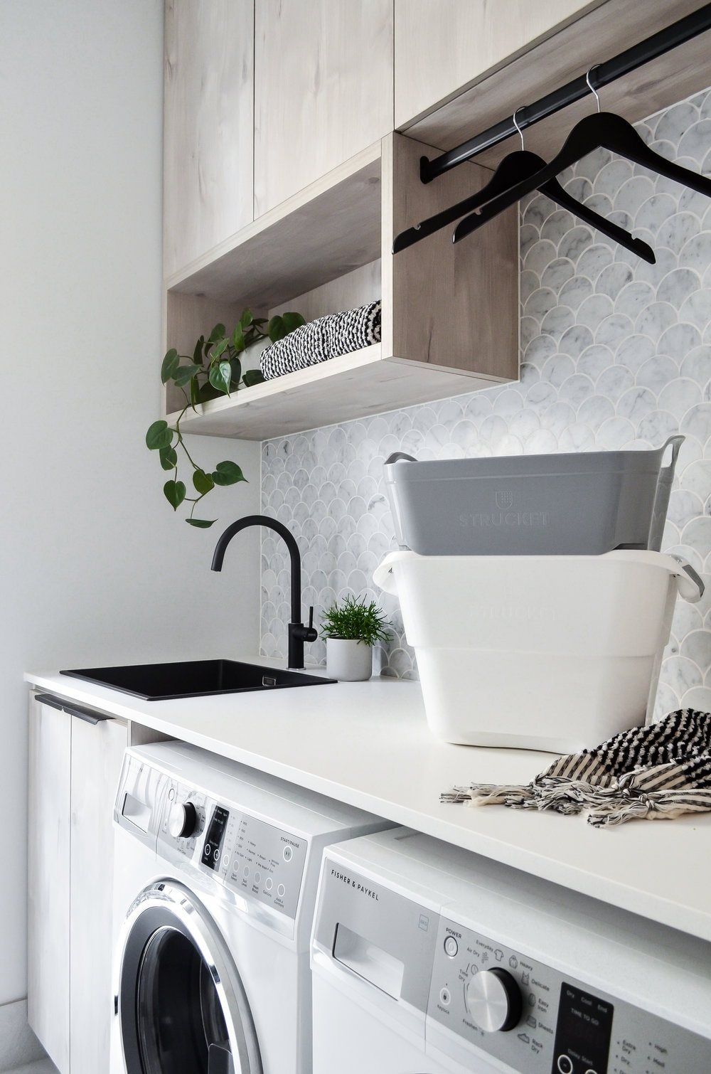 marble laundry tile with black tap and sink in modern laundry