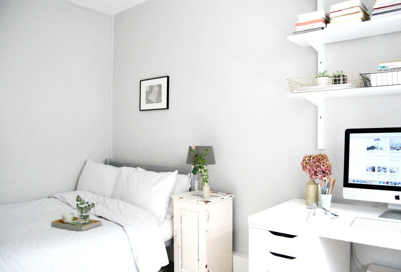 white home office and guest bedroom with all white furniture and bed against wall