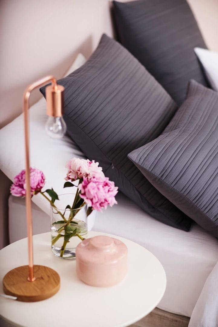 Grey Bedding with round side table and pink and gold vignette from lorraine lea