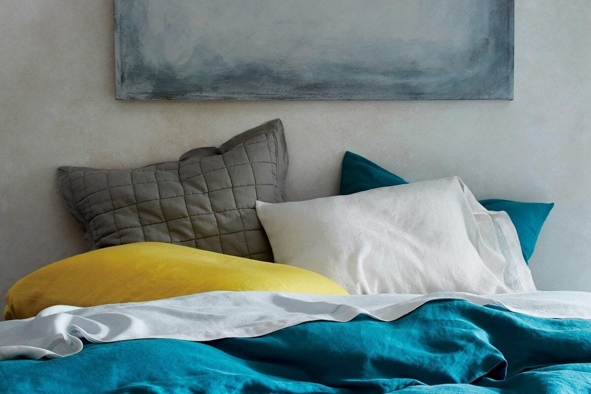bedroom pillow styling with yellow grey white and turquoise bedding set from west elm