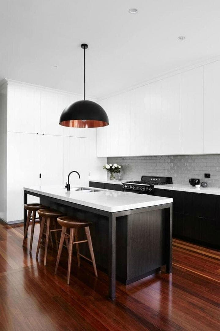 black and white kitchen with red mahogany floorboards and glossy subway tiles on kitchen splashback