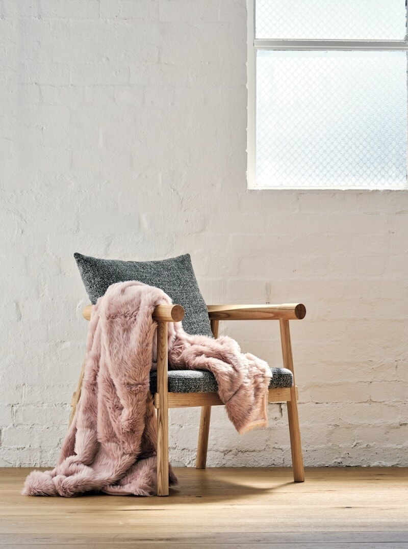blush faux fur throw on charcoal and blonde timber armchair with exposed white brick wall