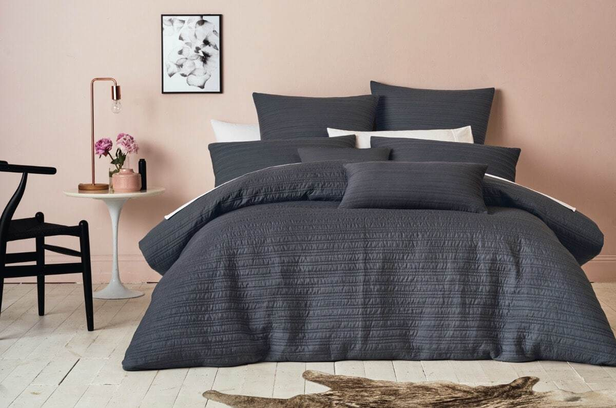 blush feature wall in bedroom with charcoal bedding set and copper lamp on bedside